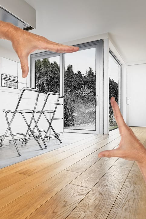 Planned renovation of an ADU. Hands creating a border in the interior of a living room with french windows and garden outside