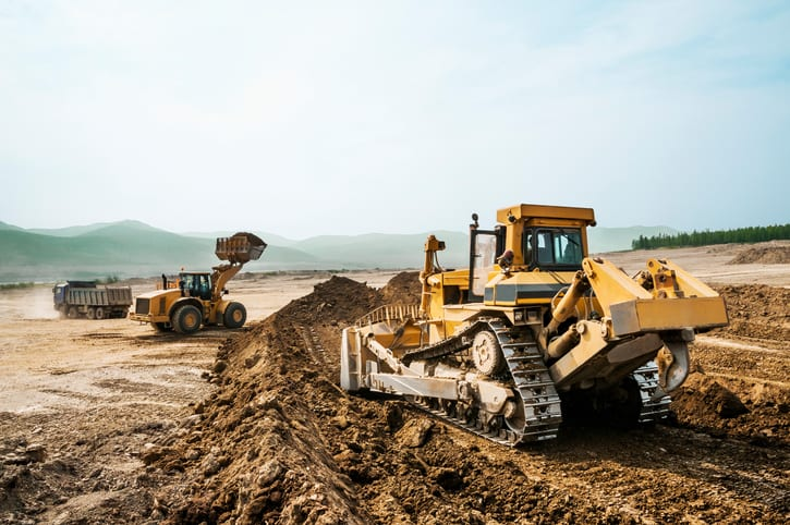 Bulldozers and front end loader working on a summer day, land disruption concept