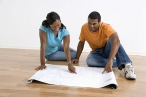 Couple sitting on floor looking at architectural blueprints.