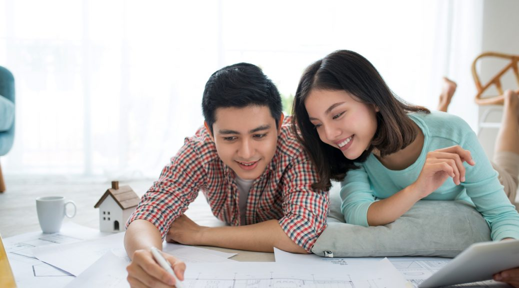 Attractive young asian adult couple looking at blue prints for an ADU in Hawaii.