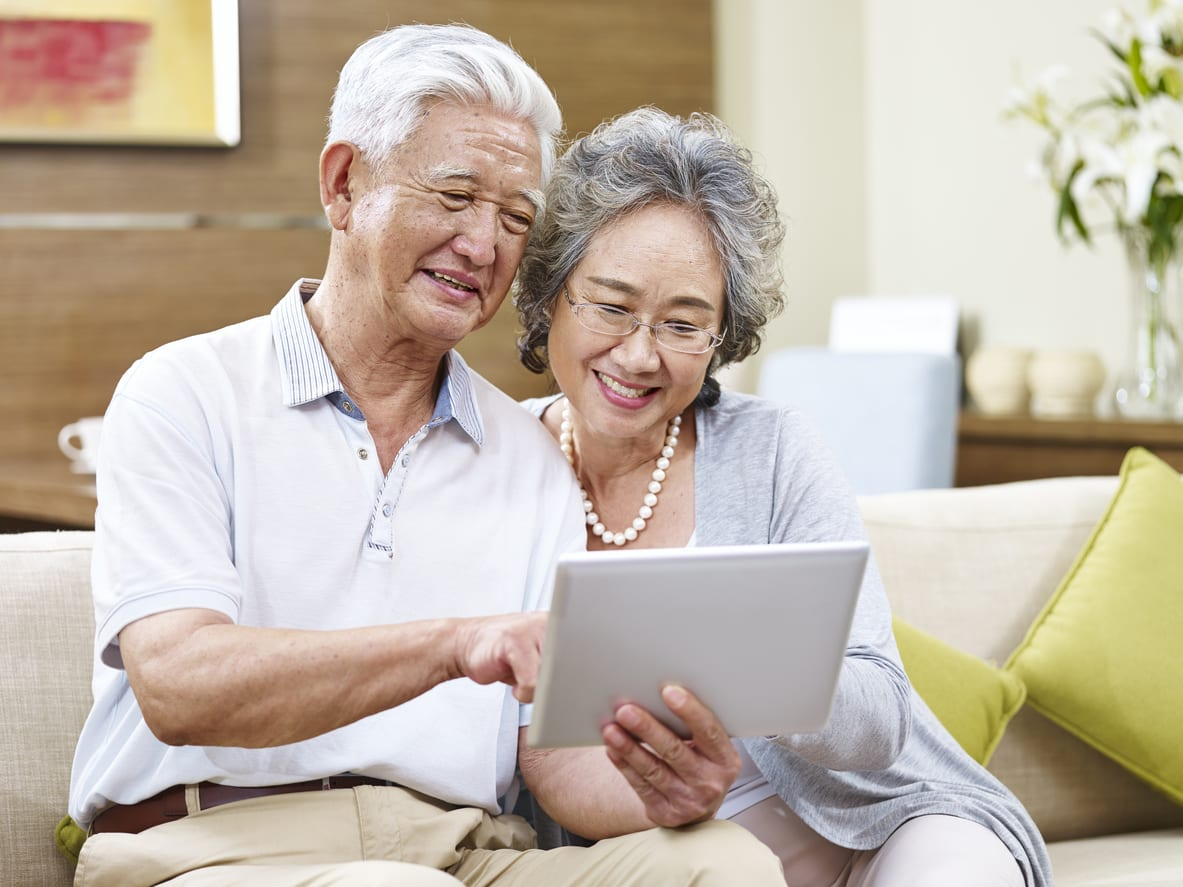 senior asian couple looking at plans for an ADU on a tablet computer at home
