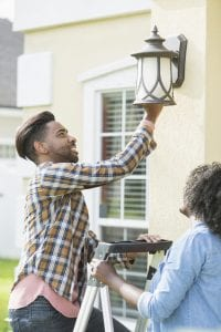 A young multi-ethnic couple doing house repairs and maintenance. They are standing with a ladder under a light fixture, changing the light bulb.